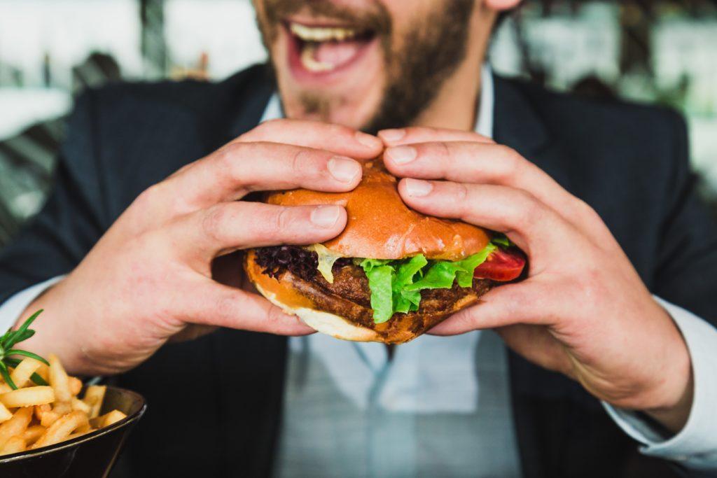 ハンバーガーを食べようとするビジネスマン