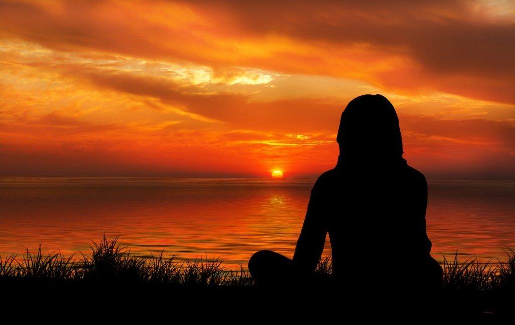 夕焼けを見ながら瞑想する女性