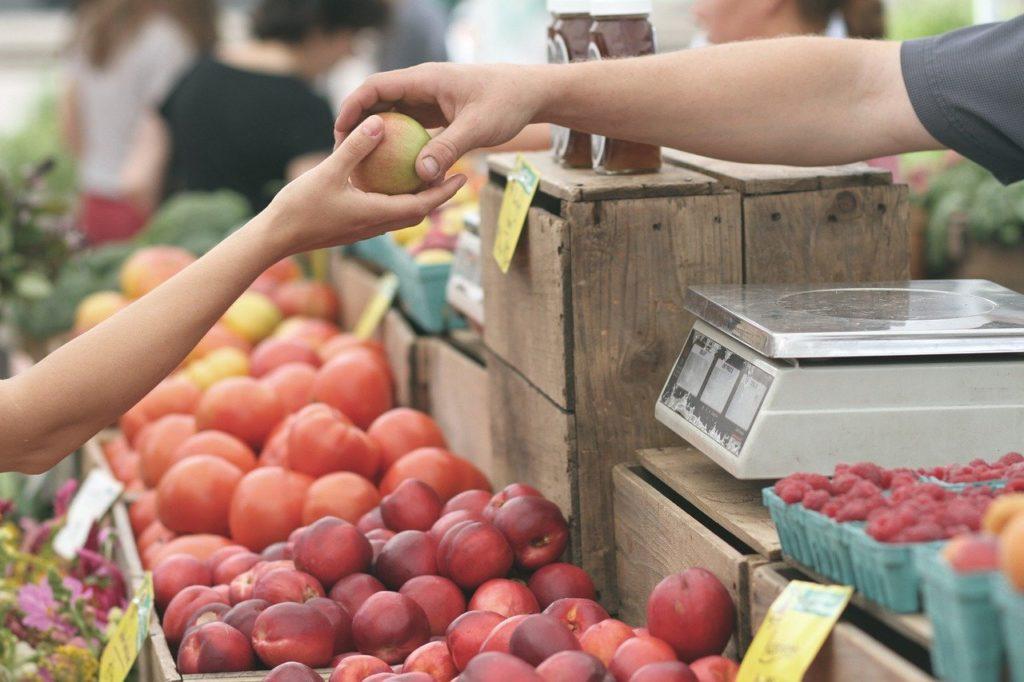 りんごを手渡す(市場)
